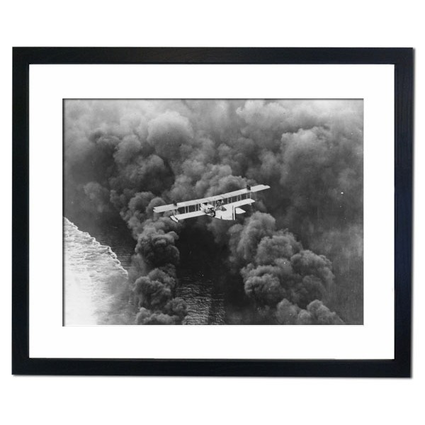 A striking aerial picture of a US Naval seaplane balanced over a dense smoke screen, California 1927 Framed Print
